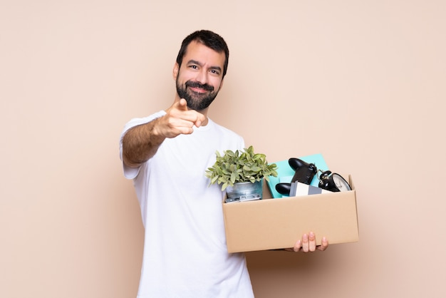 El hombre que sostiene una caja y se muda a un nuevo hogar sobre una pared aislada le señala con una expresión de confianza