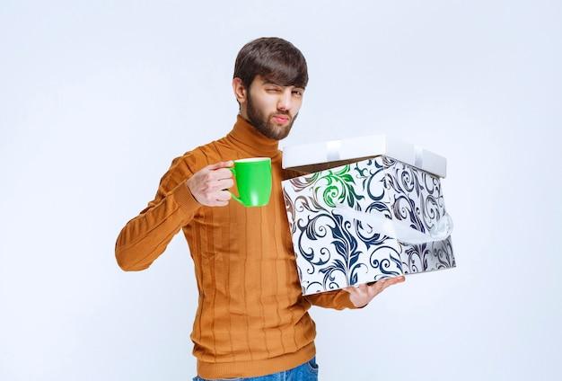 Hombre que sostiene una caja de regalo azul blanca y una taza verde de café de satisfacción.
