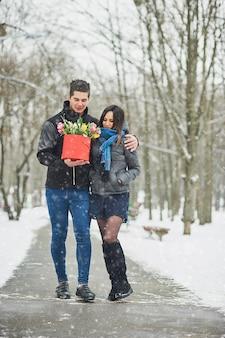 Hombre que sostiene la caja de regalo roja con un hermoso ramo de tulipanes en flor de color rosa, amarillo y blanco y crisantemos blancos con hojas verdes, al aire libre