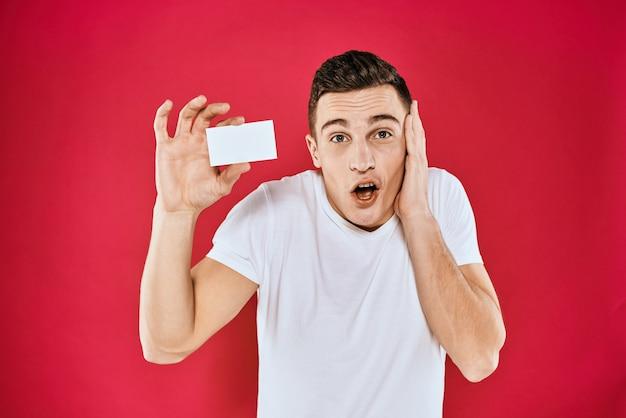 Hombre que sostiene la camiseta blanca del espacio del café del administrador de la tarjeta de visita fondo rojo aislado