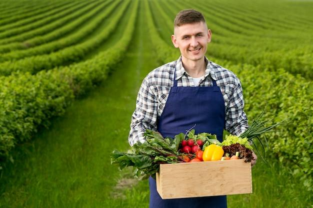 Hombre que sostiene la canasta con verduras