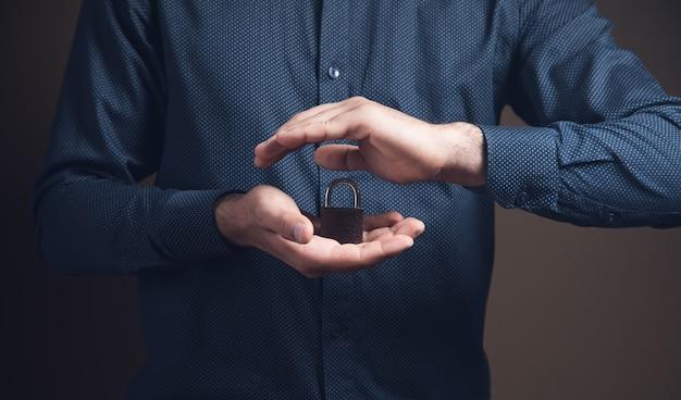 Un hombre que sostiene un candado en sus manos en forma de protección sobre una superficie marrón