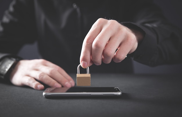 Hombre que sostiene el candado en el teléfono inteligente. seguridad