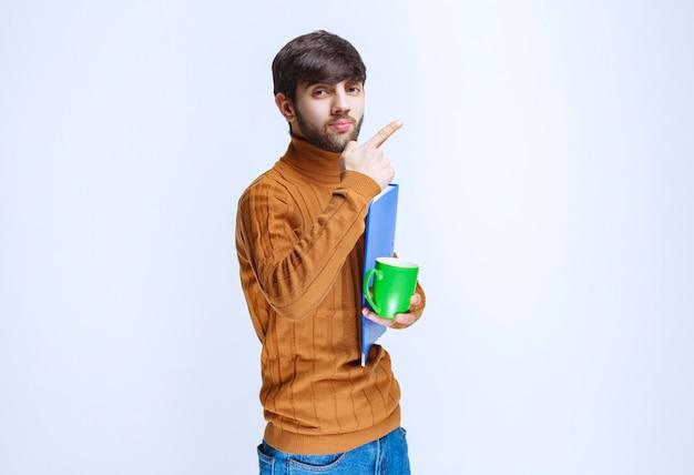 Hombre que sostiene una carpeta azul y una taza de bebida verde.