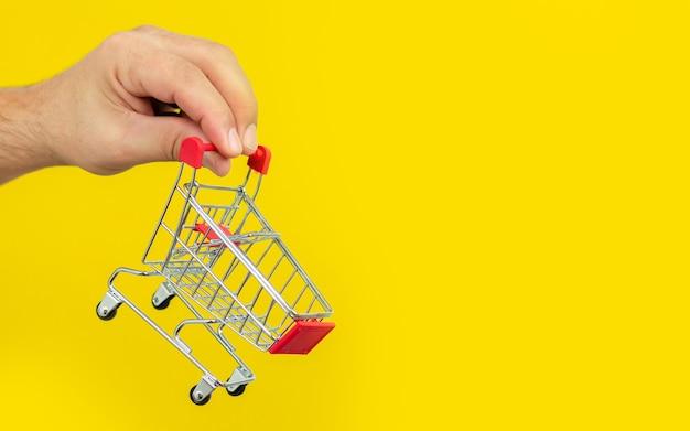 Hombre que sostiene la carretilla del carro de la compra pequeño en fondo amarillo de moda. concepto de compras