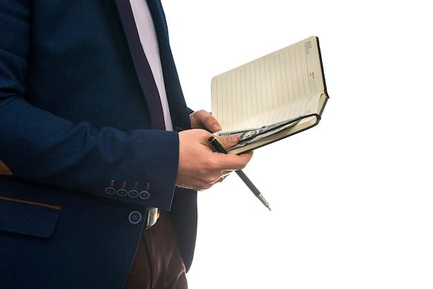 Hombre que sostiene un contrato de compra o arrendamiento de signos de cuaderno abierto con efectivo aislado.