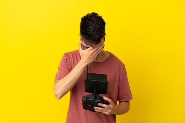 Hombre que sostiene un control remoto de drone aislado sobre fondo amarillo con expresión cansada y enferma