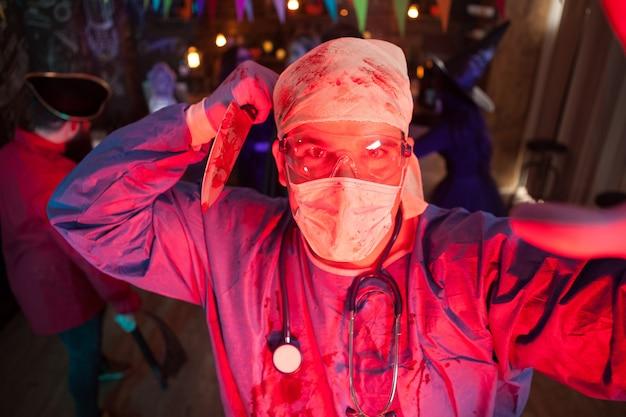 Hombre que sostiene un cuchillo cubierto de sangre vestido como un médico espeluznante en la fiesta de halloween. disfraz de halloween. amigo disfrazado de monstruos en el fondo.