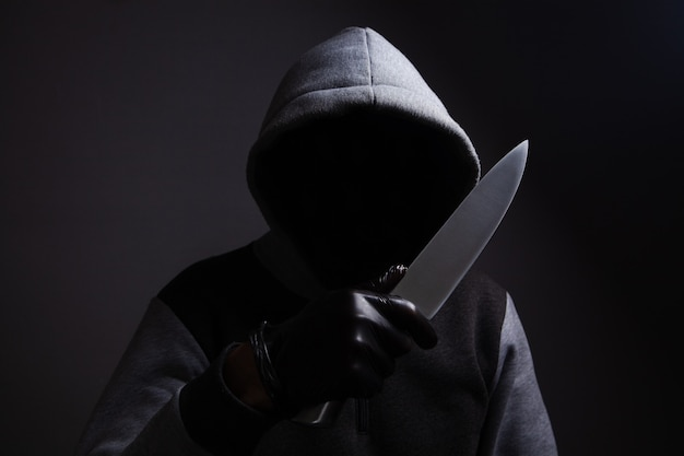Un hombre que sostiene un cuchillo grande amenaza