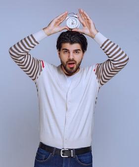 Hombre que sostiene un despertador entre las palmas.