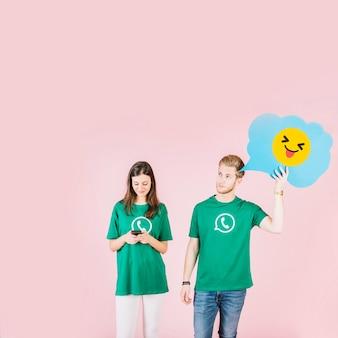 Hombre que sostiene el emoticon con la lengua hacia fuera al lado de la mujer que usa el teléfono móvil