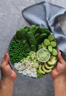Hombre que sostiene la ensalada verde vegetariana cruda sana en el fondo de piedra