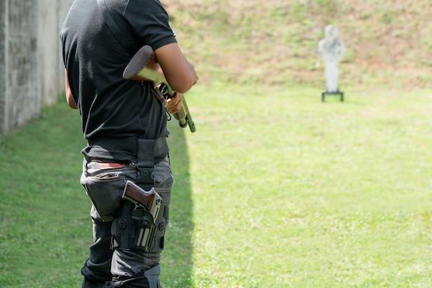 El hombre que sostiene la escopeta y lleva la pistola en la pantorrilla al frente de target en el campo de tiro.