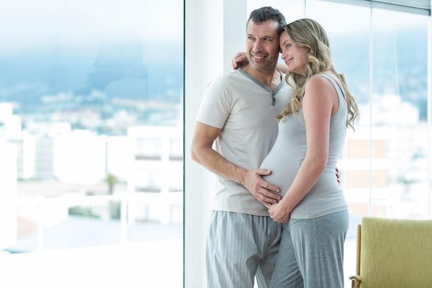 Hombre que sostiene el estómago de la mujer embarazada en el dormitorio