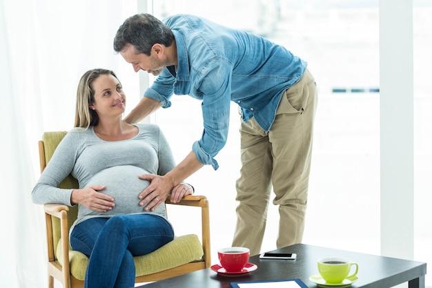 Hombre que sostiene el estómago de la mujer embarazada en la sala de estar