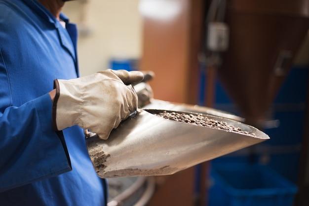 Hombre que sostiene los granos de café tostados en primicia. café aromático fresco listo para la venta. obrero en uniforme y guantes
