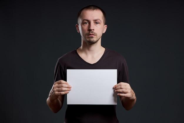 Hombre que sostiene una hoja de papel vacía en sus manos