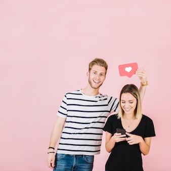 Hombre que sostiene el icono del amor sobre la mujer feliz que usa el teléfono inteligente