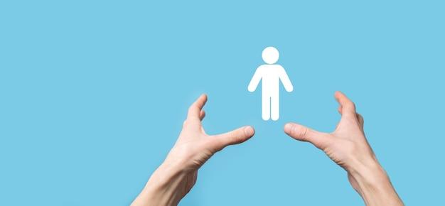 Hombre que sostiene el icono humano en la superficie azul. recursos humanos.