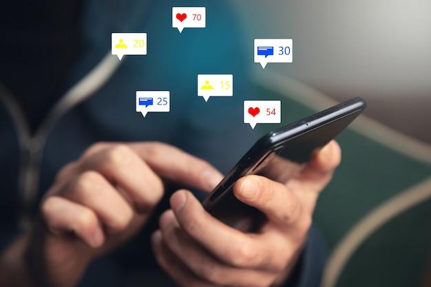 Hombre que sostiene los iconos de redes sociales con teléfono inteligente