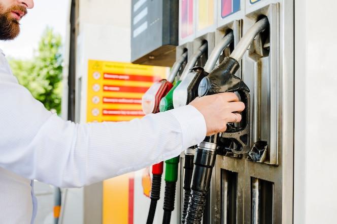Hombre que sostiene la boquilla de combustible en una estación de servicio