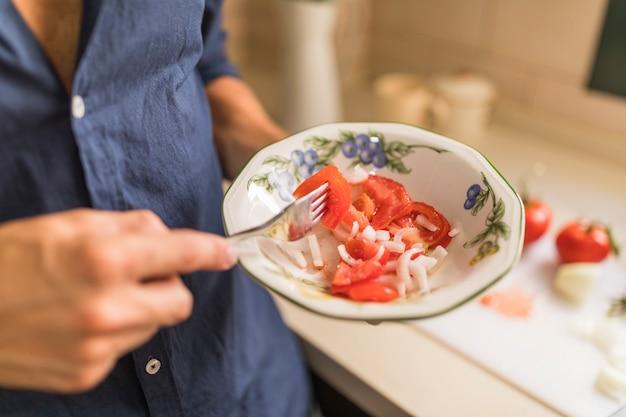 Hombre que sostiene la rodaja de tomate con un tenedor en el cuenco