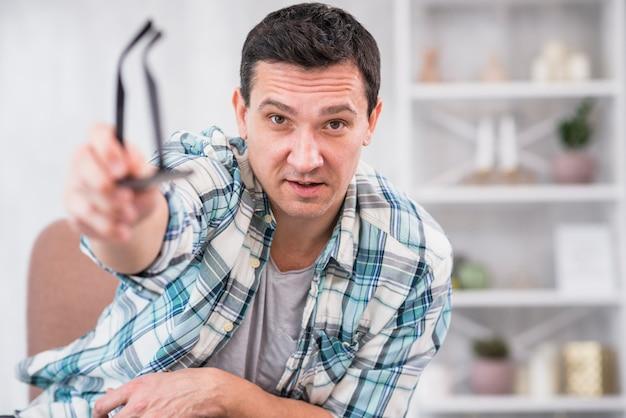El hombre que sostiene las lentes en estiró la mano en silla en casa