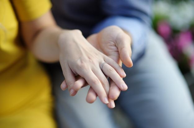 Hombre que sostiene la mano de la mujer con la boda o el anillo de compromiso