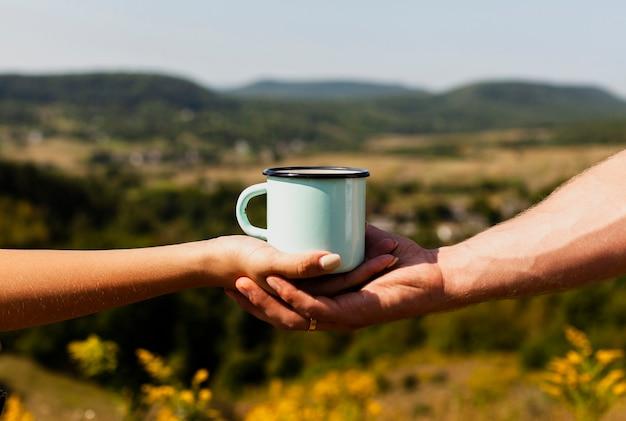 Hombre que sostiene la mano de la mujer y una taza de café