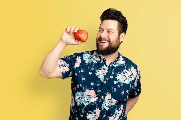 Hombre que sostiene la manzana para la campaña de alimentación saludable