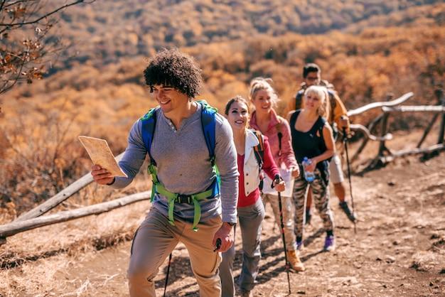 Hombre que sostiene el mapa y líder pequeño grupo de excursionistas.