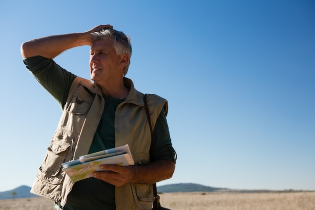 Hombre que sostiene el mapa en el paisaje