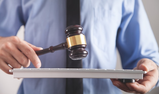 Hombre que sostiene el mazo del juez con el teclado de la computadora. concepto de delito en internet