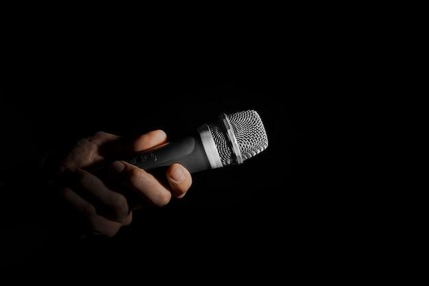Un hombre que sostiene un micrófono sobre una superficie negra.
