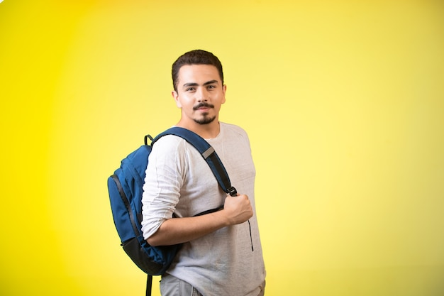 Hombre que sostiene una mochila azul y parece coqueto.