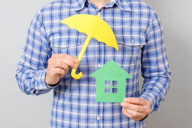 Hombre que sostiene el modelo de la casa. concepto para seguro de hogar