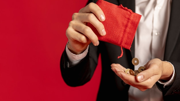 Hombre que sostiene monedas de oro con bolsa roja para año nuevo chino