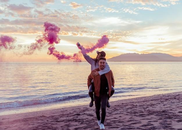 Hombre que sostiene a la mujer con la bomba de humo rosa en la espalda en la orilla del mar