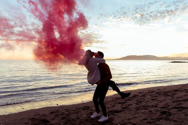Hombre que sostiene a la mujer en brazos con la bomba de humo rosa en la orilla del mar