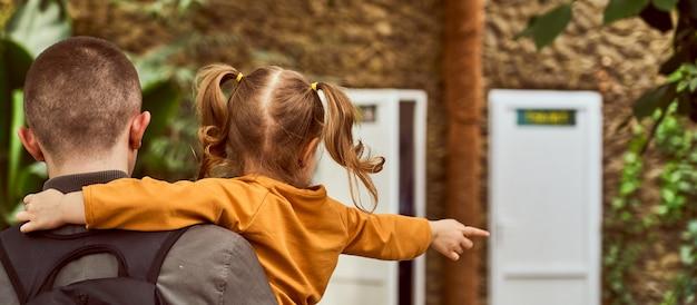 Un hombre que sostiene a un niño en sus brazos, de vuelta en el marco, vaya. el niño señala con un gesto