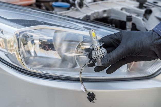 Hombre que sostiene la nueva bombilla halógena auto moderna para su reparación. equipo automotriz