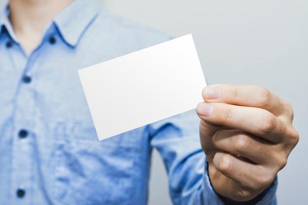 Hombre que sostiene el papel de la tarjeta blanca sobre blanco, plantilla de maqueta