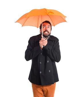 Hombre que sostiene un paraguas sobre el fondo blanco