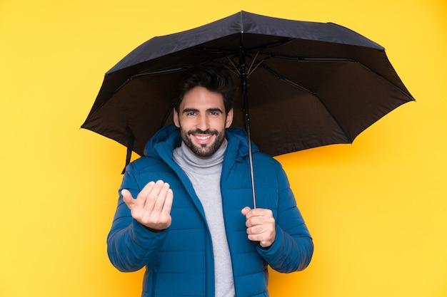 Hombre que sostiene un paraguas sobre la pared amarilla aislada que invita a venir con la mano. feliz de que hayas venido