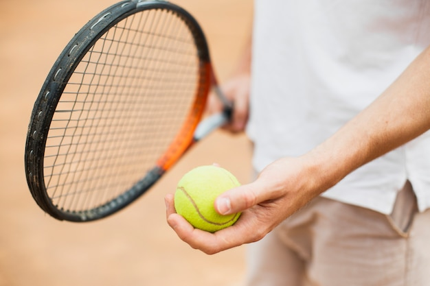 Hombre que sostiene la pelota de tenis y la raqueta