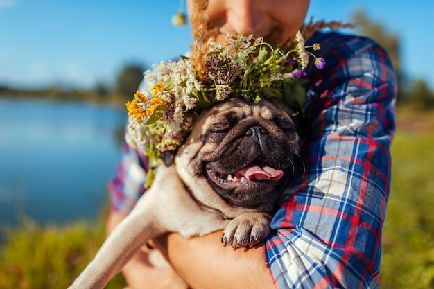 Hombre que sostiene el perro pug con corona de flores en la cabeza. hombre caminando con mascota por el lago de verano