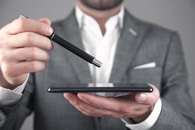 Hombre que sostiene la pluma y el teléfono inteligente. concepto de tecnología
