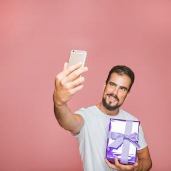 Hombre que sostiene presente tomando selfie contra fondo rosa