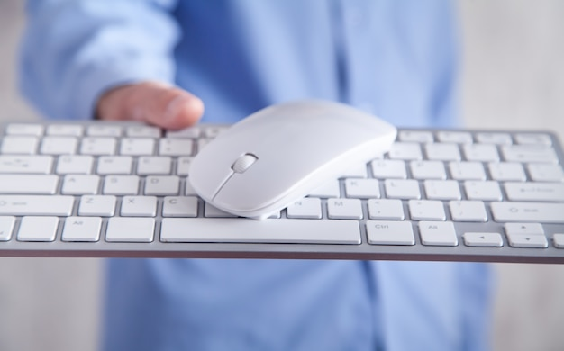 Hombre que sostiene el ratón de la computadora con un teclado. tecnología, negocios