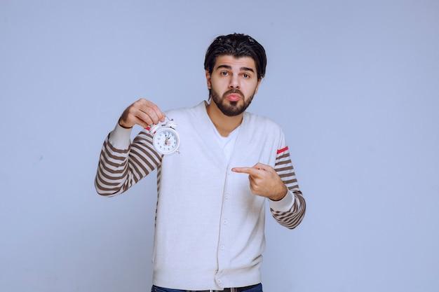 Hombre que sostiene un reloj de alarma y parece confundido.